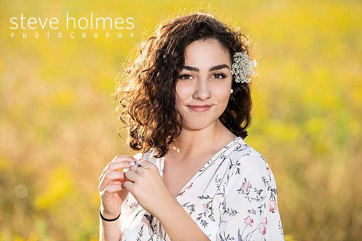 12_Curly haired brunette poses in a field with wildflowers for senior photo.jpg