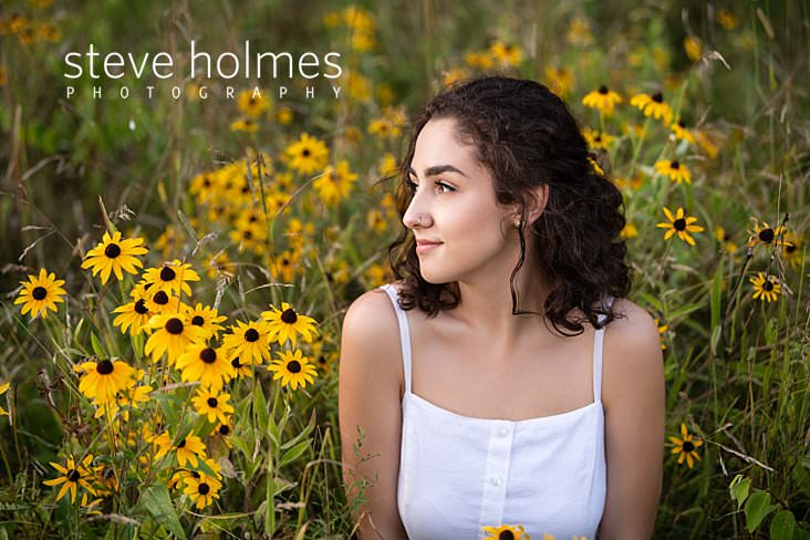 17_Curly haired brunette poses in a field with wildflowers for senior portrait.jpg