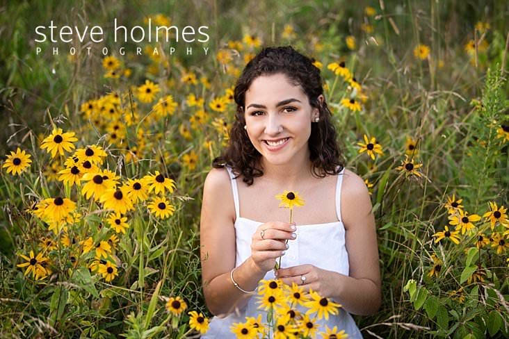 18_Curly haired brunette in poses in a field and picks wildflowers for senior portrait.jpg