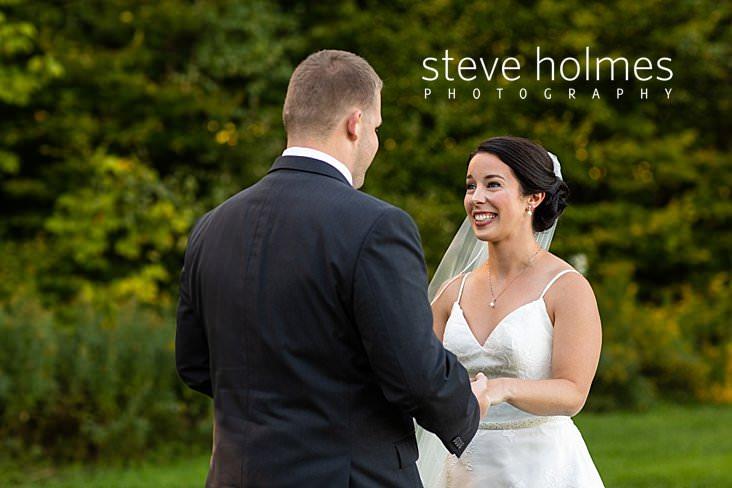 17_Excited bride smiles as groom admires her in first look.jpg