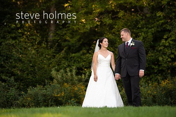 22_Bride and groom walk together outdoors.jpg