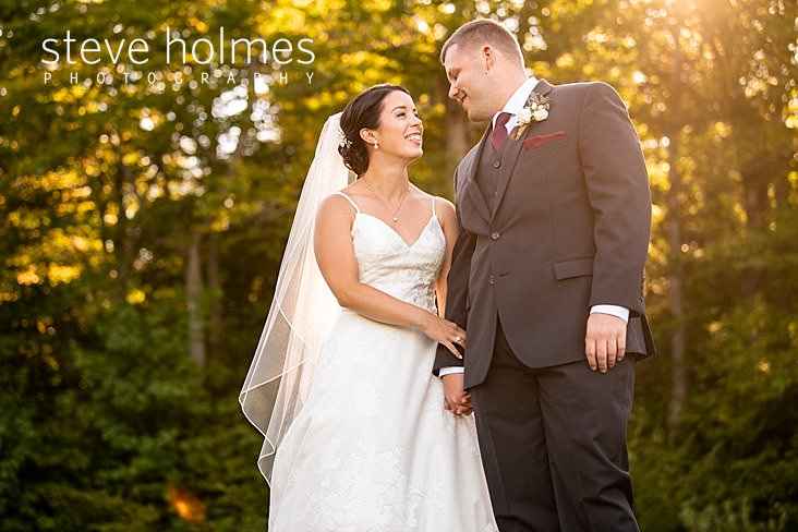 23_Bride and groom grin at each other in afternoon sunlight.jpg