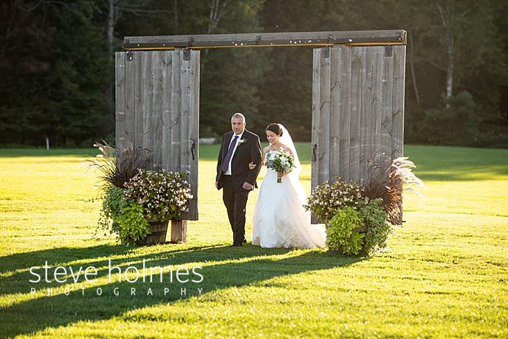 31_Bride enters outdoor wedding reception through sliding wooden doors.jpg