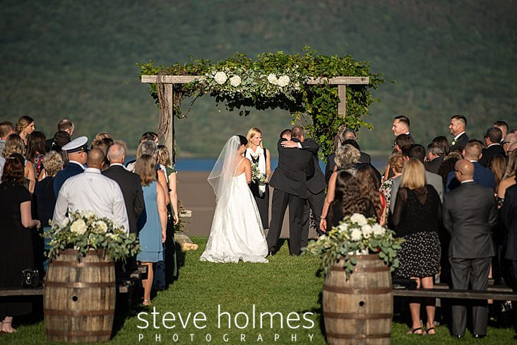 36_Father of the bride hugs groom at altar in outdoor ceremony.jpg