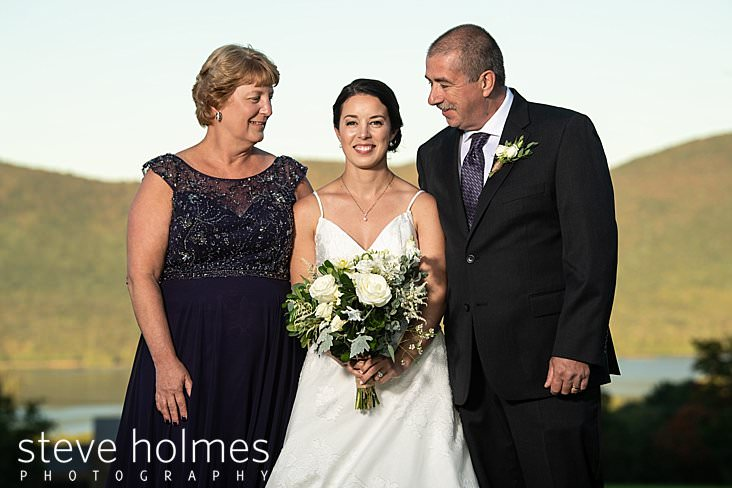 46_Bride poses with her parents outdoors.jpg