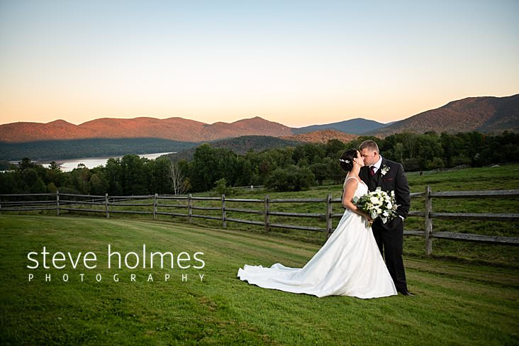 51_Bride and groom kiss next to fence and mountain range at sunset.jpg